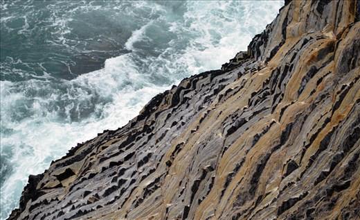 The Pacific Ocean crashes against a rigid cliff face of the Australia coastline.