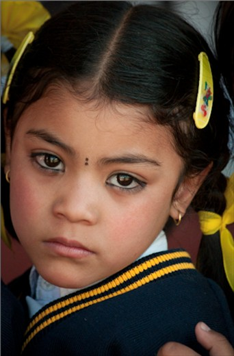 A young Nepalese girl, dressed in her school uniform. She attended the same private school in Kathmandu that the orphans I worked with went to, many of them on generous scholarships. Like many children in Kathmandu, the kohl around this girl's eyes is not only applied for aesthetic reasons but to protect her against the evil eye.