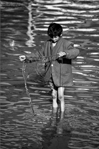At the Pashupati Hindu Temple in Kathmandu, this young street boy, armed with a rope and magnet, fishes for coins (used as funeral offerings) in the holy waters of the Baghmati River, amongst the cremated remains of corpses.