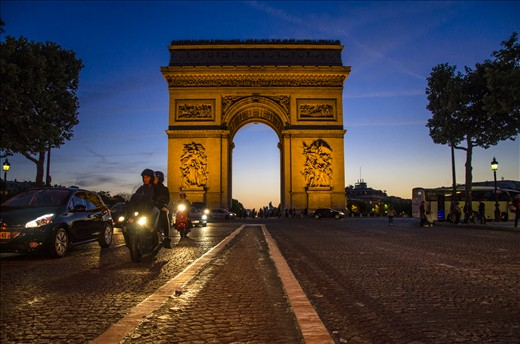 Sun Sets behind the Arc de Triumph and traffics buzzes on the Champs Elysees.