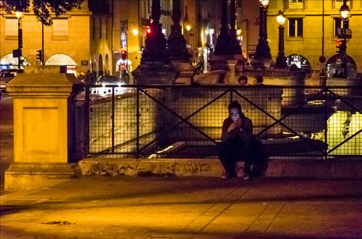 A man texts his girlfriend while smoking on Pont Neuf.