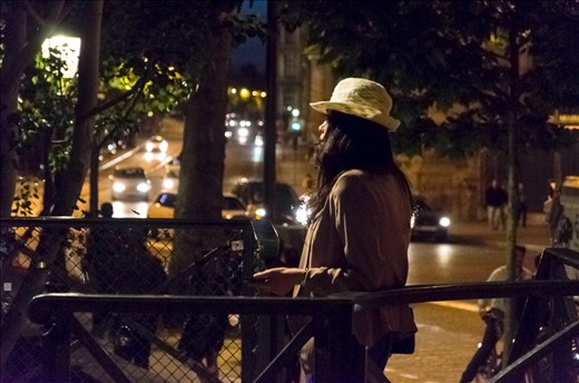 A woman waits for her date by the Pont des Arts over the Seine River.