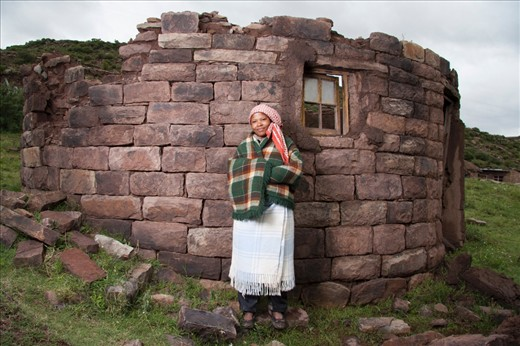 The journeys of daily life in the villages near Masitise in Lesotho, Africa.  The lady stands next to a demolished hut in her village. She is wearing blankets to face the cold in the Mountains.