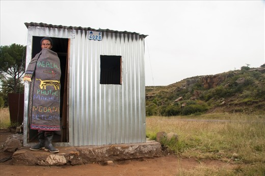 This Basotho young man poses next to his improvised shack.   Inside, there is only space for a long banch and wood stove, to help keep him warm through out the day.  He is also a cattle herder and he is wearing a blanket, that he did the embroidering himself.