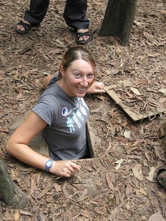 A tight squeeze, Catherine emerging from the Cu Chi Tunnels.