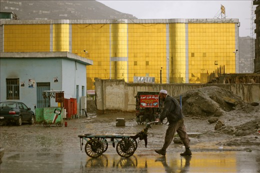 A man pushes a cart in the rain past one of Kabul's many wedding halls. 
