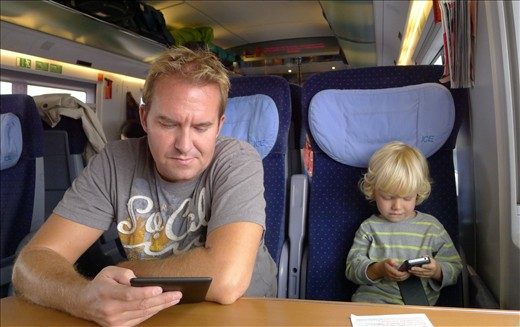 Like Father like Son - both engrossed in their electronics on train to Luxembour