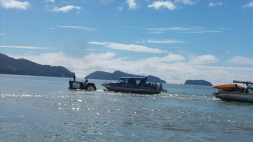 Tractor pulling the water taxi boat and trailer into the sea