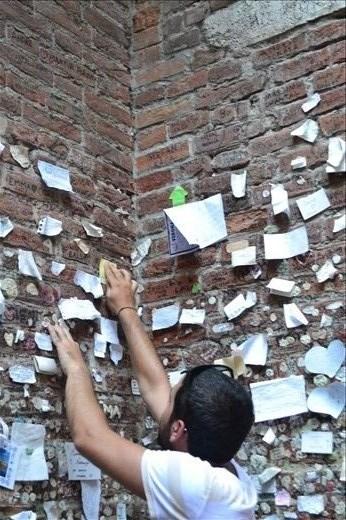 Man leaving a note by Juliette's balcony, Verona