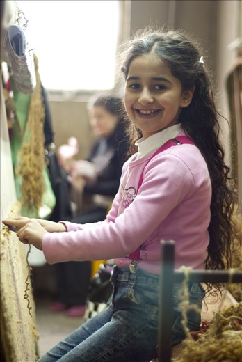 The little girl helps her grandmother to make a carpet.