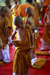 3) After taking their vows, this young boy tepidly examines his new garments. The monks help each boy to dress in their new saffron coloured robes, which signify their new life's path.