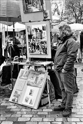 A man stands beside his artwork at Place du Tertre. He is one of the many artists who flock to Montmartre's most popular square in order to sell homemade masterpieces to passing tourists.: by claires, Views[141]