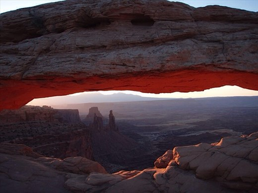 Mesa Arch lighting up at sunrise, in Canyonlands