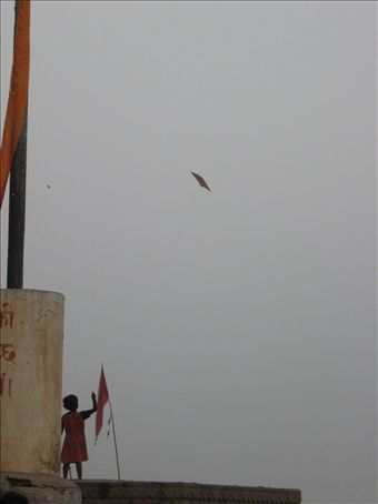 A sweet little girl flying her hand made kite in the wind on the main ghat
