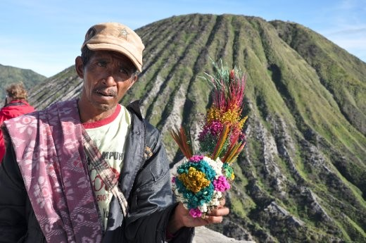 In an effort to 'appease the Gods',  locals sell bunches of flowers to tourists atop the still-steaming, active volcanic rim of Mt. Bromo.  As the legend goes, throwing the flowers into the volcano acts as a sacrifice and keeps the volcano from erupting again.