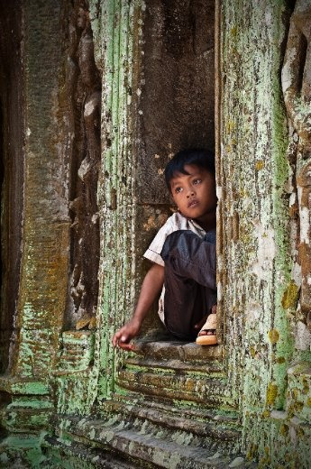 While walking through the Wat's of Siem Reap i noticed this boy nestled among the ruins dreaming, thinking, waiting for the time to pass
