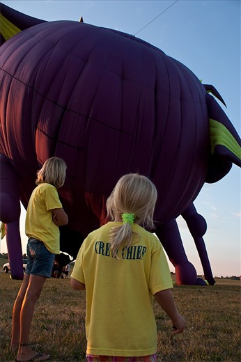 """Mother and daughter from a """"regular shaped"""" balloon crew watch as the special shaped balloon,"""