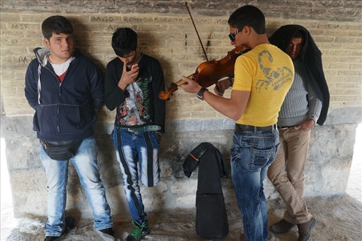 Under a historic bridge in the ancient city of Isfahan, a group of music enthusiasts enjoys the melodies emerging from a violin. In the Islamic republic, the ban on alcohol and the enforced separation of unrelated men and women uniquely shape the leisure time the youths spend during their Nowruz holidays.
