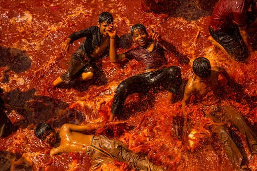 Children play in a pool of dyed water in a Hindu temple during a Holi ritual