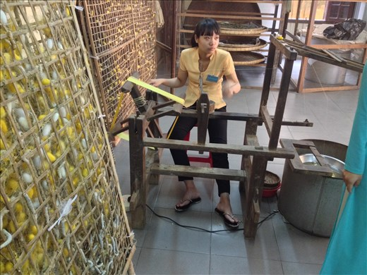 Watching silk fabric made from the worms cocoons at the Thang Loi silk factory.