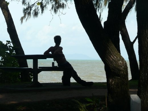 A local enjoys the cool shade of the trees as the sun over Palm Cove gets hotter, Queensland, Australia.