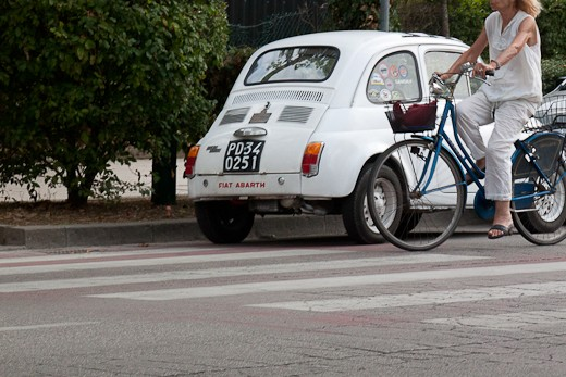 Spirito di Lido: A woman rides her bicycle by a Fiat Abarth in Lido on a hot summer's day.
