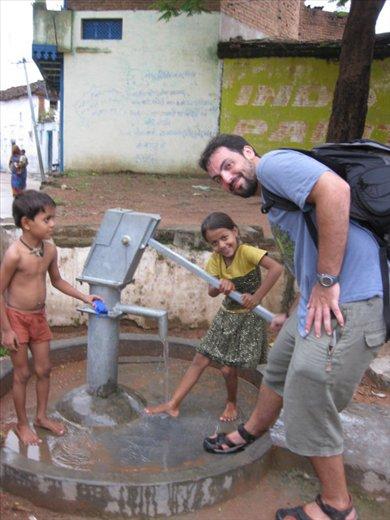 En una bomba de agua de la ciudad vieja de Kajuraho, mojándome los pies con unos niños