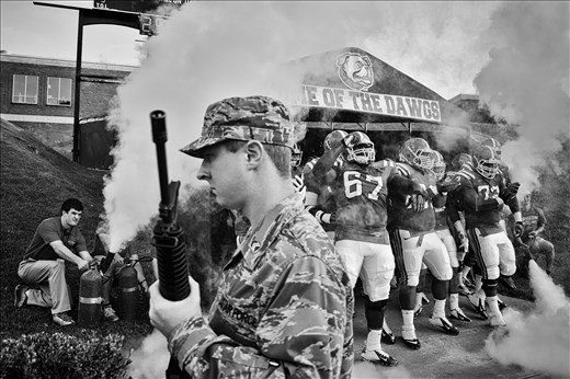 An ROTC stands guard a university football team comes on to play.