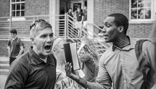 A college student with a Bible argues with an evangelist.
