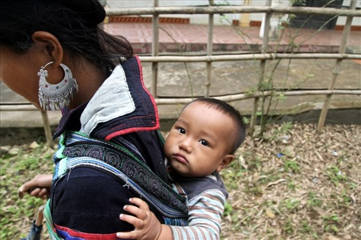 A young member of the Black H'mong tribe in Northern Vietnam looks on as his mother carries him on her back during their daily five hour trek from the town of Sapa to their home village.