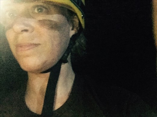 Dina sporting helmet, headlamp, and warrior-style face mud in Fossil Cave.
