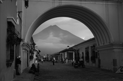 Dominating the skyline, the Volcano of Water in Guatemala stands guard over the city of Antigua, seen here though the Santa Catalina Arch.