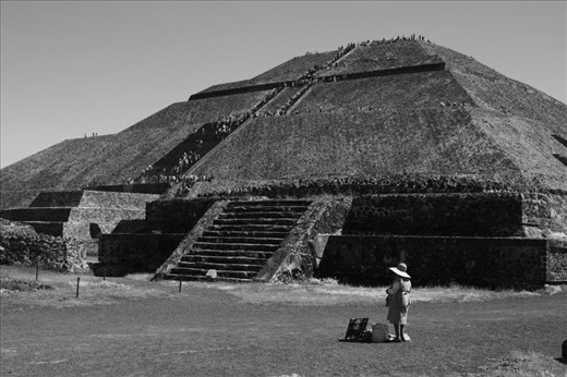 The third largest pyramid in the world known as the Pyramid of the Sun, which is located on the avenue of death in Teotihuacan near Mexico City. We can see  a steady stream of visitors passing through, as a lonely vendor waits for customers.