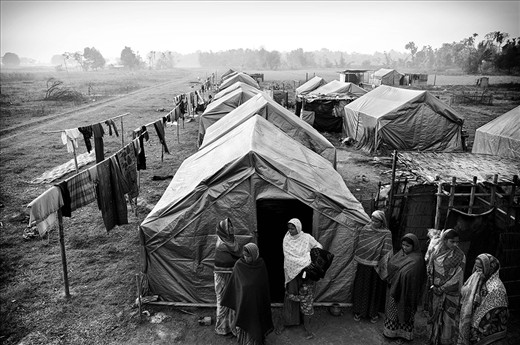 A group of women stand outside one of the tents in the camp. Out of the 600 families, less than one fourth have returned. Vacillating between debris and dreams of what used to be, they battle everyday, rebuilding bamboo by bamboo, towards a bricked structure. They hope for not much, but a house they can live in.