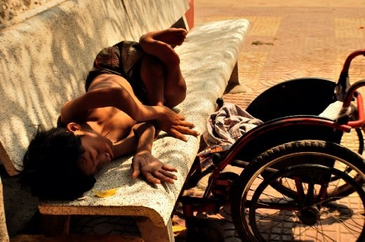 A poor, physically challenged boy with twisted limbs, who roams around Phnom Penh on a wheelchair. Getting some rest on a bench half under a tree in a bright, sunny afternoon.