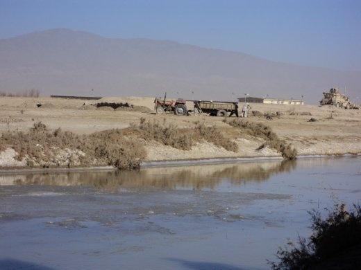 Afghan farmers trying to set free their sunken trailer near the Khandaq River.