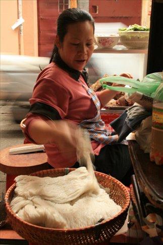 Lady making a pho bo dish.