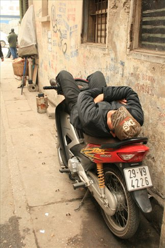 Man sleeping on a motor bike along Tam Thuong Street.