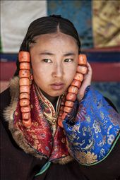 A young girl supports the coral beads from pulling on her hair as she waits to parade, for the best part of three days, in the Lurol Festival.: by doss, Views[618]