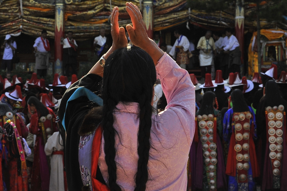 A woman raises her arms in prayer to the Mountain God Amyesrmachen, who is temporarily manifested in a human medium .