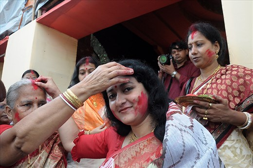 WOMEN FOLK OF BENGAL GREETS EACH OTHERS FOREHEAD WITH VERMILION. A RITUAL.