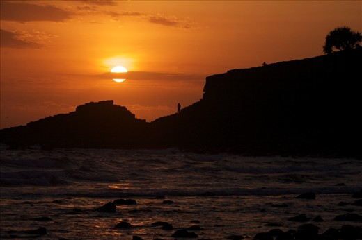 A hot summer sun rises over Fingal headland to bathe the coast in warmth.
