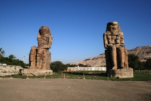 Colossi of Memnon - twin statues depict Amenhotep III . Made from blocks of quartzite sandstone, they reach a towering 18m and weigh  700 tons each. ie. BIG