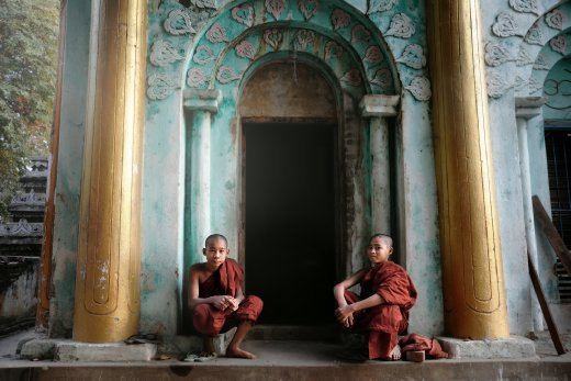 Two novice monks sit together outside an ancient temple in Sagaing, Myanmar.  This grand and ornate temple is in the grounds of their monastery, a place where monks of all ages grow up together, forming a brotherhood of close connections.