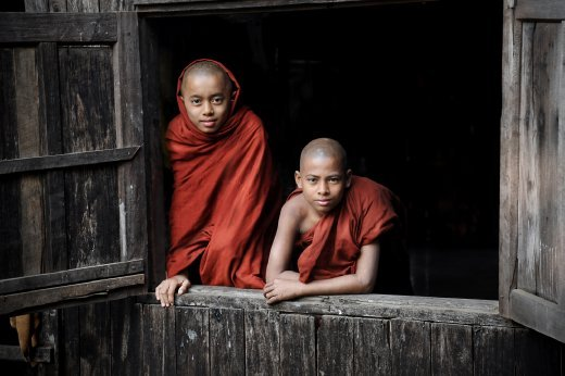 Inside their teak monastery, two novice monks rest by a large window, characteristic of these ancient buildings.  Taken in the town of Sittwe, Myanmar.