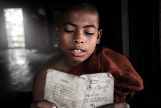 A novice Monk in Sittwe, Myanmar, prays from a well used prayer book in his ancient teak monastery. The traditions of Buddhism are upheld very strongly today in Myanmar, and monks pray throughout the day to honour the teachings of the Buddha.