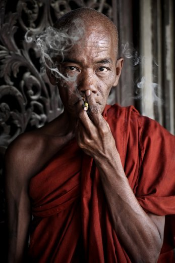 A monk from Mandalay, Myanmar, smokes in front of his old teak monastery.  Not many monks do smoke, except for some in the older generations.
