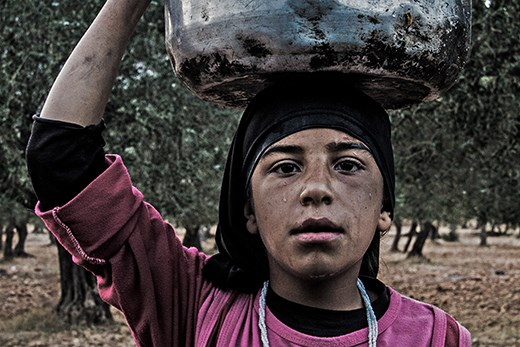 A YOUNG GIRL putting on her head a Cooking pot filled by wa PUTTING ON HER HEAD