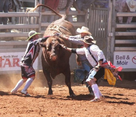 Two bull fighters undoing a hung up cowboy