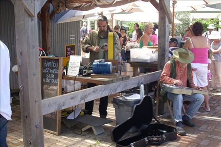 At the saturday market. Greg is playing his slide guitar (on right) and a man is sharpening tools on the left.